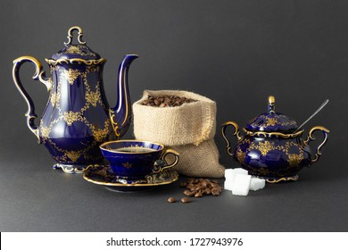 Still life with a beautiful cobalt blue colored vintage porcelain coffee set with golden floral pattern, a sugar bowl and a gunnysack filled with roasted coffee beans on dark gray background.