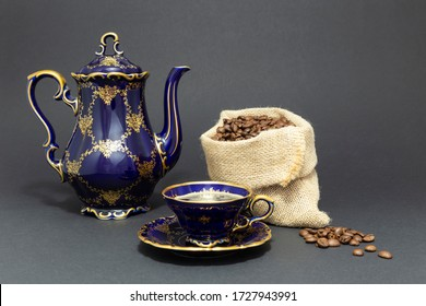 Still life with a beautiful cobalt blue colored vintage porcelain coffee set with golden floral pattern and a gunnysack filled with roasted coffee beans on dark gray background.