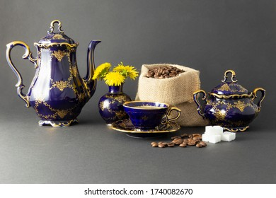 Still life with a beautiful cobalt blue colored vintage porcelain coffee set with golden floral pattern, a sugar bowl, a flower vase and a gunnysack filled with roasted coffee beans.