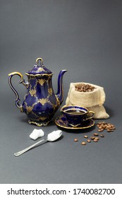 Still life with a beautiful cobalt blue colored vintage porcelain coffee set with golden floral pattern, a silver spoon with sugar cubes and a gunnysack filled with roasted coffee beans.