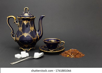 Still life with a beautiful cobalt blue colored vintage porcelain tea set with golden floral pattern, spoon with sugar cubes and dry tea leaves.