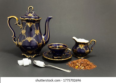 Still life with a beautiful cobalt blue colored vintage porcelain tea set, spoon with sugar cubes, milk jug and dry tea leaves.