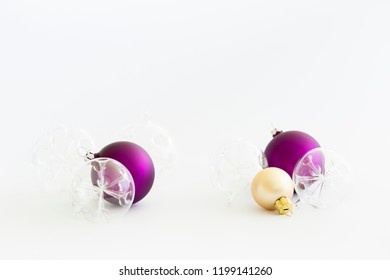 Still life with beautiful decorative transparent and purple christmas glass balls on white background