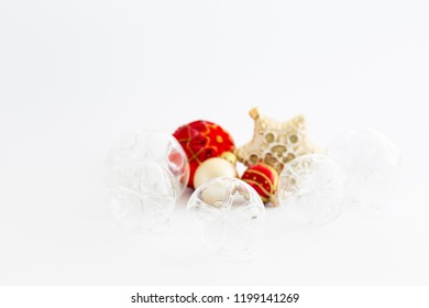 Still life with beautiful decorative transparent and red christmas glass balls and a satin colored star ornament on white background