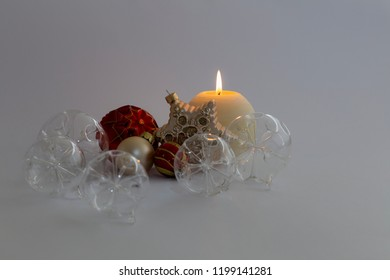 Still life with beautiful decorative transparent and red christmas glass balls, a round satin colored burning candle and a satin star ornament on gray background
