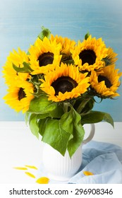 Still life with beautiful sunflowers bouquet in white vase on blue wooden background. Greeting card concept.