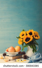 Still life with beautiful sunflowers bouquet in white vase with apples, pine cones and book on blue wooden background. Retro style toned. Greeting card concept.