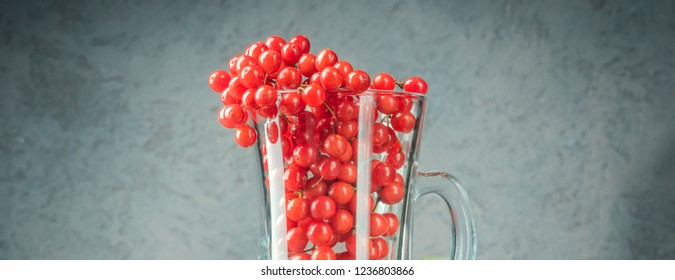 Still life berries of a viburnum in a glass and honey on wooden table. Autumn concept food agriculture, harvesting, warming drinks, cooking