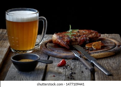 Still life with big fried steak, a glass of beer, mustard and cutlery on an old wooden tabletop, the concept of Oktoberfest and St. Patrick's Day