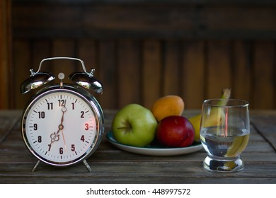 Still life with a big old alarm clock, fruity breakfast and a glass of water, a wooden background