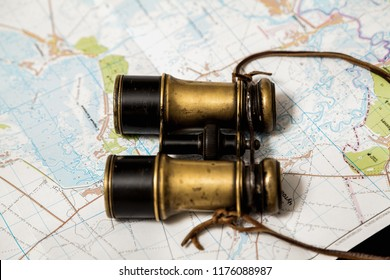 Still life with binoculars and a map. Vintage metal binoculars lie on topographic map of the area
