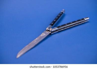 still life- black butterfly knife on blue ground