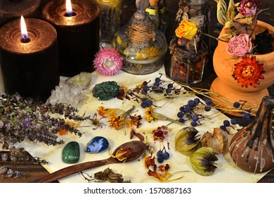 Still life with black candles, dry healing flowers and herbs on old paper on witch table. Esoteric, wicca and occult background, fortune telling and divination ritual, mystic concept