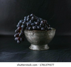 Still life with black grapes in a metal bowl