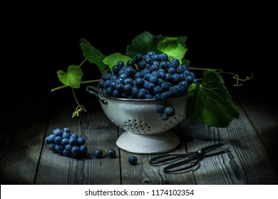 still life with black grapes in an old colander on rough wooden table