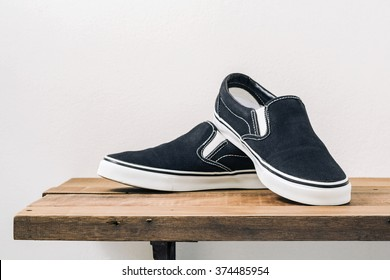 Still life with black slip-on casual shoes on wood table