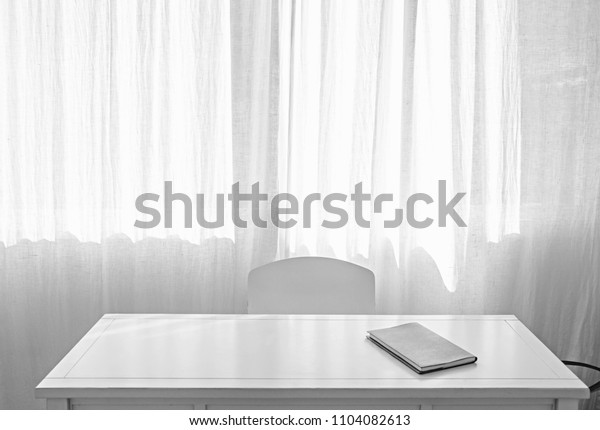 Still life black and white home office  work desk and empty chair against light window space, new job position inviting workplace, working from home, indoors. Paperwork folder on work table, interior.