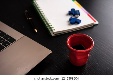 still life with block note, laptop, pen and a red cup of coffee over a black office desk. symbol of job