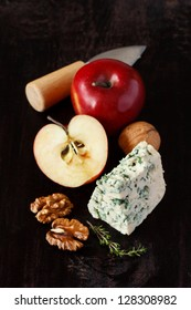 Still life with blue cheese, apples and walnut on a dark background.
