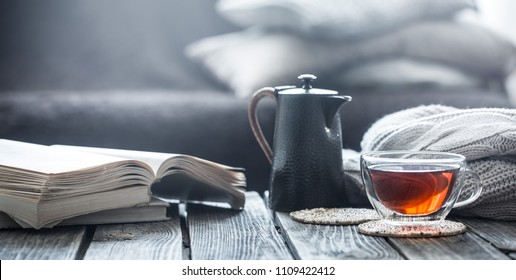 still life book and a cup of tea in the living room on a wooden table, the concept of coziness and interior