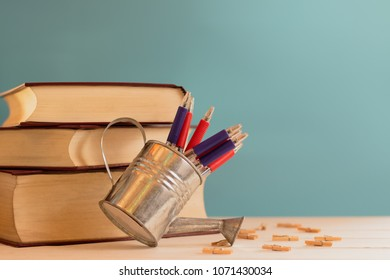still life of books and  many pens on the desk,table with light green background.