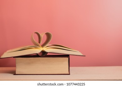 still life of books stack,a heart shape of book pages with pink pastel color for background.