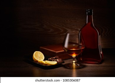 Still life with bottle of cognac, glass with cognac and plate with pieces of lemon and chocolate standing on a table on a dark wooden background.