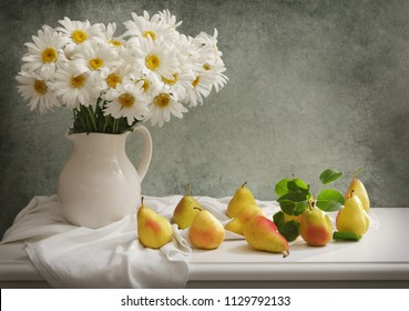 still life with bouquet of daisy flowers in a jar and fresh pears on wooden table