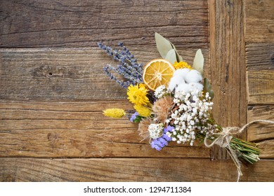 Still life of bouquet of dried flowers with orange segment on wooden background