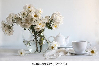 still life with a bouquet of fall flowers and tea set
