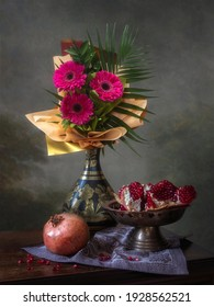 Still life with a bouquet of flowers and pomegranates