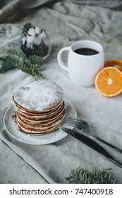 A still life of breakfast scene, that includes traditional american pancakes topped with maple syrup and sugar powder, a cup of black coffee and oranges