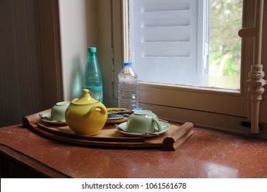 Still life: bright yellow sugar bowl, two classic turned cups on saucers of delicate light green color, set of colored tea, coffee, two bottles of water on marble window sill (glass with old handle)
