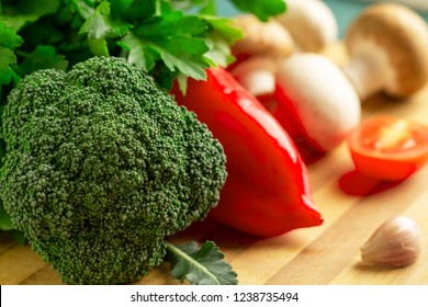 Still life of broccoli, pepper, tomato, champignons, royal champignons, garlic, parsley lies on a wooden kitchen board. Focus on broccoli inflorescence.
