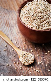 Still life  with buckwheat grain heap in wooden bowl on vintage wooden table background. Organic healthy eating cuisine. Vegan gluten free buckwheat cereal diet.