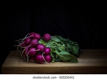 Still life bunch of radish on black dark background