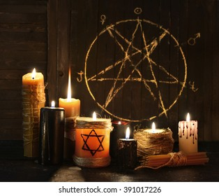 Still life with burning candles against pentagram circle background. Black magic ritual with occult, evil and esoteric symbols. Halloween or divination rite