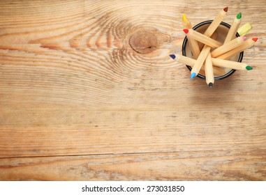 Still life, business, education concept. Pencils in a mug on a wooden table. Selective focus, copy space background, top view