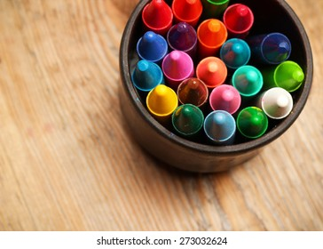 Still life, business, education concept. Crayons in a mug on a wooden table. Selective focus, top view