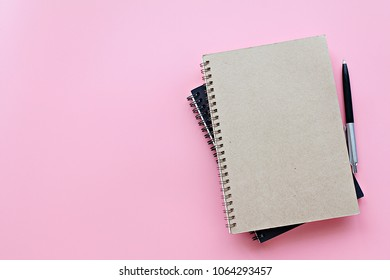 Still life, business, office supplies or education concept : Top view or flat lay of notebooks and pen on pink background, ready for adding or mock up