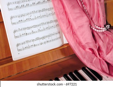 Still life with cabinet piano,score, shawl and bead