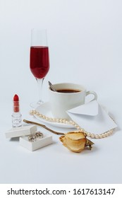 A still life with a ceramic cup of coffee, a faded rose, a coral necklace, a lipstick, a box with the silver earrings, a white envelop, and the glass of champagne isolated on a white background.