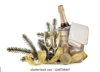 Still life with champagne bottle  standing  in a bucket with ice, two full champagne flutes and Christmas ornaments  isolated on a white background with copy space, Christmas and New Year celebration