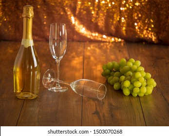 Still life with champagne and two glasses and cluster of green grapes on a wooden surface, Golden glittering background, Warm tones.