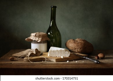 Still life with cheese, bread and milk
