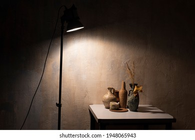still life with a clay jug of squash and squash in the dark under lamp light
