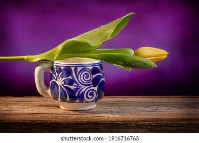 Still life of a closed yellow tulip placed on a blue and white Mexican pottery cup on a barn wood table in front of a purple backdrop