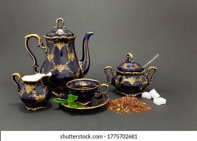 Still life with a cobalt blue vintage porcelain tea set, spoon with sugar cubes, sugar bowl, milk jug and dry tea leaves.