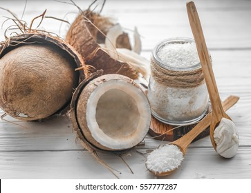Still life with coconut and coconut flakes in wooden spoons and glass jar on wooden background
