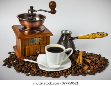 Still life with coffee attributes. Coffee grinder,  Cup, coffee beans.